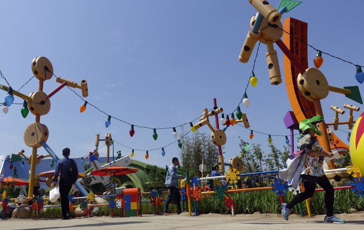 Visitors walk through Toy Story Land during its grand opening at Shanghai Disneyland in Shanghai, China, Thursday, April 26, 2018. Walt Disney Co. stressed its deep China connections as it opened an extension of Shanghai's $5.5 billion Disney Resort on Thursday amid escalating tensions over trade and technology between Beijing and Washington. (AP Photo/Erika Kinetz)