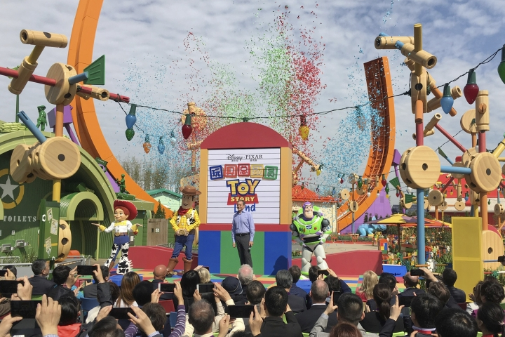 Disney CEO Robert Iger, center, stands as confetti drops during the grand opening of Toy Story Land at Shanghai Disneyland in Shanghai, China, Thursday, April 26, 2018. Walt Disney Co. stressed its deep China connections as it opened an extension of Shanghai's $5.5 billion Disney Resort on Thursday amid escalating tensions over trade and technology between Beijing and Washington. (AP Photo/Erika Kinetz)