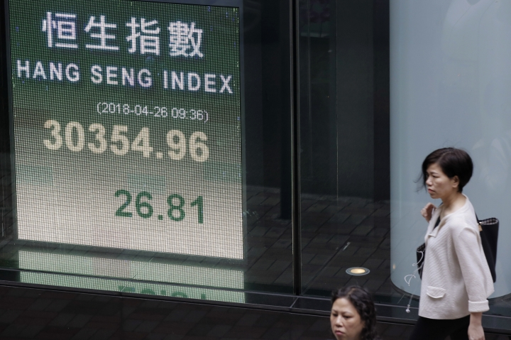 A woman walks near an electronic board showing Hong Kong share index outside a bank in Hong Kong, Thursday, April 26, 2018. Asian stock markets were mixed on Thursday as investors digested the latest quarterly corporate earnings. (AP Photo/Kin Cheung)