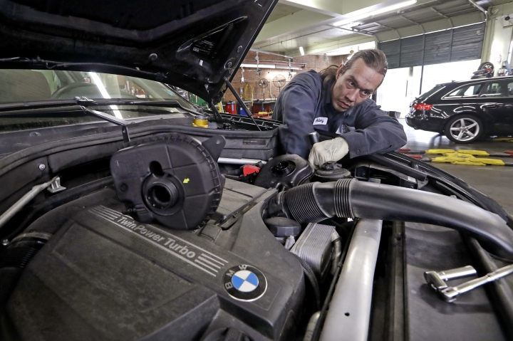 In this Wednesday, April 25, 2018, photo, auto technician Anthony Sterns works to replace the coolant expansion tank on a 2011 BMW at the Fat City German Car service shop in Seattle. At first, dumping your old car might seem like a no-brainer, and you can't help picturing how good you would look in that new car. But automotive experts say you'll almost always come out ahead, at least financially, by fixing old faithful. (AP Photo/Elaine Thompson)
