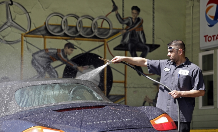 In this Wednesday, April 25, 2018, photo, worker Carlos Gomez sprays a car to try to help find a leak at the Fat City German Car service shop in Seattle. At first, dumping your old car might seem like a no-brainer, and you can't help picturing how good you would look in that new car. But automotive experts say you'll almost always come out ahead, at least financially, by fixing old faithful. (AP Photo/Elaine Thompson)