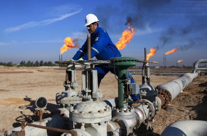 FILE - In this Thursday, Jan. 12, 2017 file photo, an Iraqi worker operates valves in Nihran Bin Omar field north of Basra, Iraq. Emerging from a grueling war with the Islamic State group for more than three years, Iraq plans to open more of its untapped oil and gas resources to foreign developers to boost reserves and to increase sorely needed revenues for post-war construction by offering rights to explore and develop hydrocarbon-rich areas. (AP Photo/ Nabil al-Jurani, File)