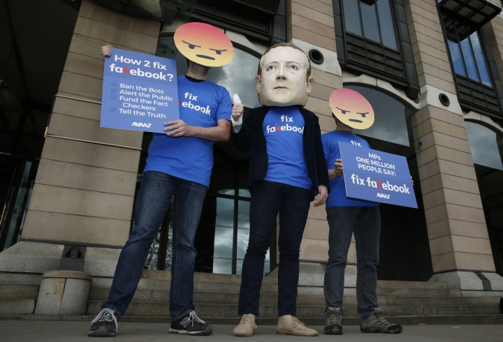 A protester wearing a mask with the face of Facebook founder Mark Zuckerberg, in between men wearing angry face emoji masks, during a protest against Facebook outside Portcullis in London, Thursday, April 26, 2018, as the Chief Technical Officer of Facebook Mike Schroepfer is due to give evidence on the companies use of data from its customers in front of a Parliamentary Select Committee. (AP Photo/Alastair Grant)