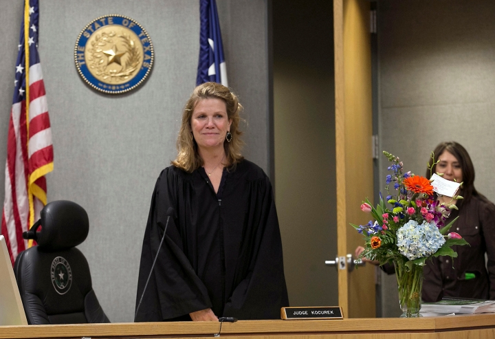 FILE - In this Feb. 29, 2016 file photo, District Judge Julie Kocurek makes her first public appearance after spending weeks recovering from an assassination attempt in November 2015, as she is welcomed back to the bench in Austin, Texas. A federal jury in Texas has found 30-year-old Chimene Onyeri guilty of several charges relating to a 2015 assassination attempt on the judge outside her home. Jurors Thursday, April 26, 2018, found Onyeri guilty of multiple counts of fraud, racketeering and other charges. Prosecutors say Onyeri as part of a racketeering enterprise shot Kocurek as she was in an SUV returning to her home. (Ralph Barrera/Austin American-Statesman via AP, File)