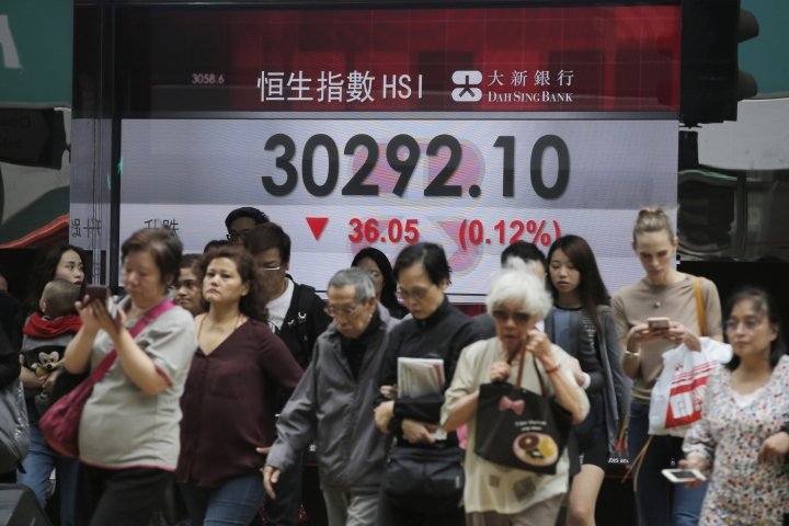 People walk past an electronic board showing Hong Kong share index outside a bank in Hong Kong, Thursday, April 26, 2018. Asian stock markets were mixed on Thursday as investors digested the latest quarterly corporate earnings. (AP Photo/Kin Cheung)