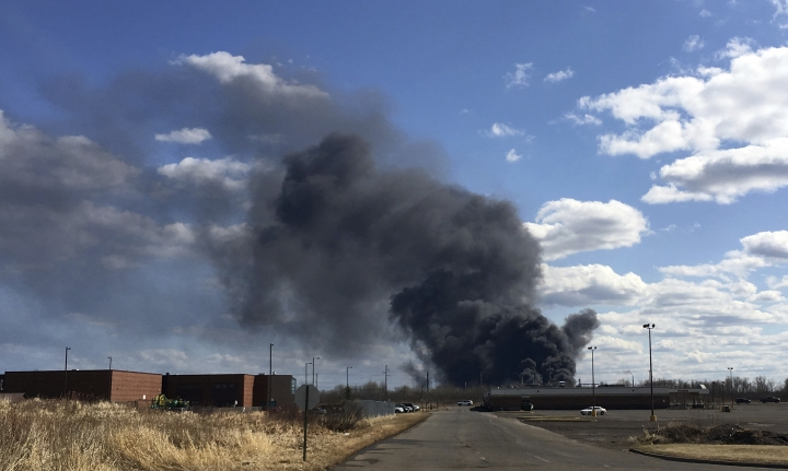 A fire at the Husky Energy oil refinery in Superior, Wis., seen from a police check point in Superior, Wis., on Thursday, April 26, 2018, rocked the refinery, injuring multiple people and forcing the evacuation of homes, schools and a hospital, and sending a plume of noxious smoke into the air. (Dan Kraker/Minnesota Public Radio via AP)