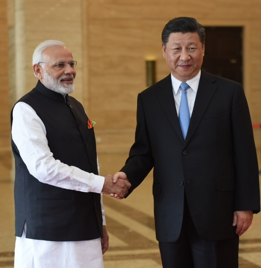 In this photo released by the Indian Ministry of External Affairs, Indian Prime Minister Narendra Modi, left, shakes hands with Chinese President Xi Jinping in Wuhan, China, Friday, April 27, 2018. The leaders of India and China met at a lakeside resort in central China on Friday amid tensions along their contested border and a rivalry for influence among their smaller neighbors that could determine dominance in Asia. (Indian Ministry of External Affairs via AP)