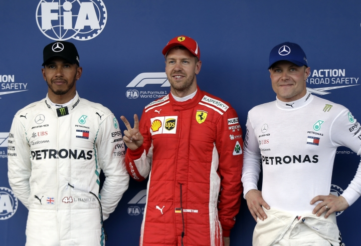 Mercedes driver Lewis Hamilton of Britain, Ferrari driver Sebastian Vettel of Germany and Mercedes driver Valtteri Bottas of Finland, from left to right, pose for photos at the end of the qualifying session at the Baku Formula One city circuit, in Baku, Azerbaijan, Saturday, April 28, 2018. The Formula One race will be held on Sunday. Vettel clocked the fastest time, Hamilton was second and Bottas third. (AP Photo/Luca Bruno)