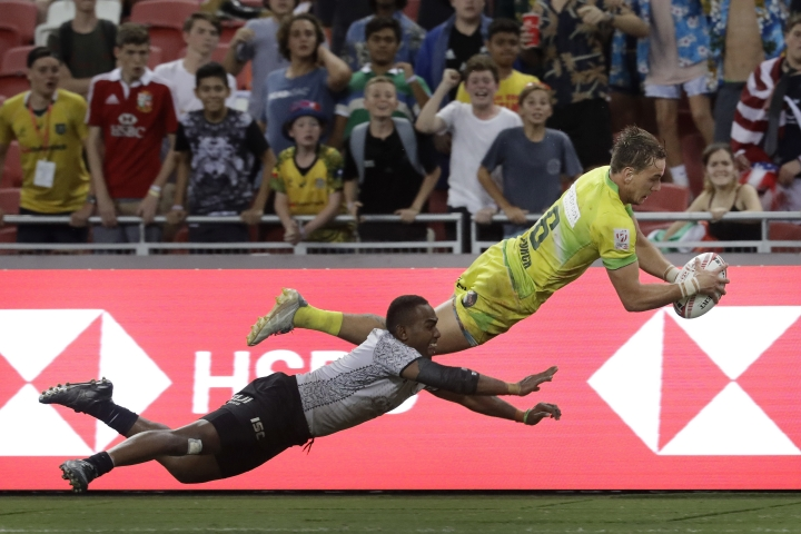Australia's John Porch, dives in to score a try while Fiji's Kalione Nasoko, tries to stop him during the HSBC World Rugby Sevens Series 2018 finals on Sunday, April 29, 2018, in Singapore. (AP Photo/Wong Maye-E)