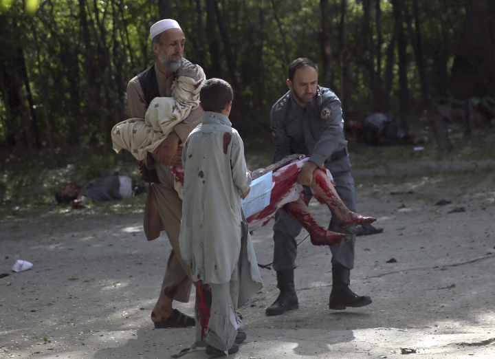 A wounded woman is helped at the site of explosions, in Kabul, Afghanistan, Monday, April 30, 2018. The explosions targeted central Kabul on Monday morning, killing people and wounding a dozen, authorities said. (AP Photo/Massoud Hossaini)