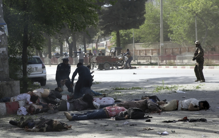 EDS NOTE GRAPHIC CONTENT - Victims in double explosions lie on the ground in Kabul, Afghanistan, Monday, April 30, 2018. The explosions targeted central Kabul on Monday morning, killing people, authorities said. (AP Photo/Massoud Hossaini)