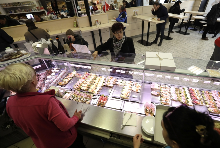 In this picture taken on Thursday, March 1, 2018, woman shops for open-face sandwiches at traditional delicatessen Golden Cross in Prague, Czech Republic. With an undying popularity, the traditional Czech open-face sandwiches have entered a new century of its existence with a respect for tradition combined with new innovative approaches. (AP Photo/Petr David Josek)