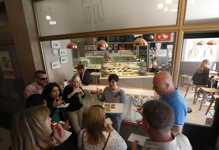 In this picture taken on Tuesday, April 10, 2018, group of tourists gets a taste of open-face sandwiches at bistro Sisters in Prague, Czech Republic. With an undying popularity, the traditional Czech open-face sandwiches have entered a new century of its existence with a respect for tradition combined with new innovative approaches. (AP Photo/Petr David Josek)