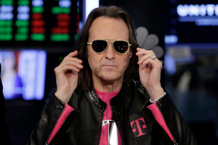 T-Mobile CEO John Legere wears Sprint-yellow sunglasses on the floor of the New York Stock Exchange, Monday, April 30, 2018. To gain approval for their $26.5 billion merger agreement, T-Mobile and Sprint aim to convince antitrust regulators that there is plenty of competition for wireless service beyond Verizon and AT&T. (AP Photo/Richard Drew)