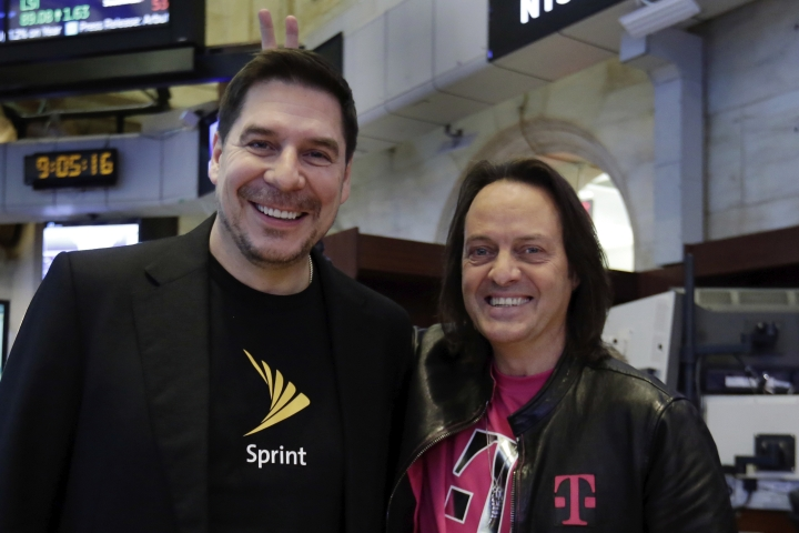 T-Mobile CEO John Legere, right, makes bunny ears behind Sprint CEO Marcelo Claure as they pose for photos on the floor of the New York Stock Exchange, Monday, April 30, 2018. T-Mobile and Sprint have been considering a combination for years, but to gain approval for their $26.5 billion merger agreement, the wireless companies aim to convince antitrust regulators that there is plenty of competition beyond Verizon and AT&T. (AP Photo/Richard Drew)