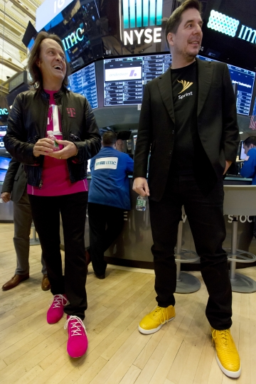 T-Mobile CEO John Legere, left, and Sprint CEO Marcelo Claure wear their signature color shoes on the floor of the New York Stock Exchange, Monday, April 30, 2018. T-Mobile and Sprint have been considering a combination for years. But a 2014 attempt fell apart amid resistance from the Obama administration. (AP Photo/Richard Drew)