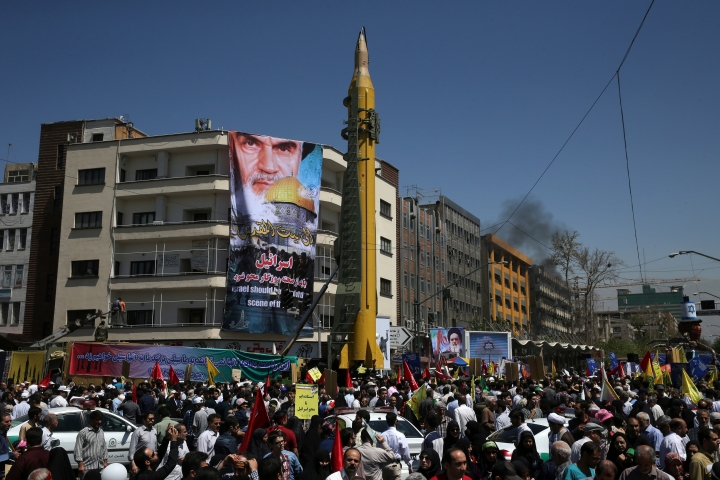 FILE - In this June 23, 2017 file photo, a Ghadr H surface-to-surface ballistic missile is displayed by Iran's Revolutionary Guard in an annual pro-Palestinian rally marking Al-Quds (Jerusalem) Day, in Tehran, Iran. Facing a second suspected Israeli strike killing Iranian forces in Syria, the Islamic Republic has few ways to retaliate as its officials wrestle both domestic unrest at home and the prospects of its nuclear deal collapsing abroad. A portrait of the late Iranian revolutionary founder Ayatollah Khomeini and Jerusalem's Dome of Rock hangs from a building in background. (AP Photo/Vahid Salemi, File)