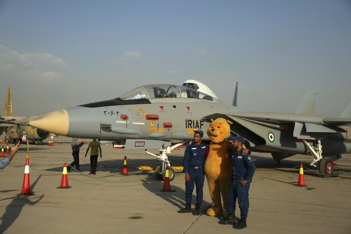 FILE - In this Sept. 23, 2015 file photo, Iranian soldiers take a picture with a Winnie the Pooh character next to a F-14 fighter jet in an exhibition of achievements and equipment of Iran's air force in Tehran, Iran. Facing a second suspected Israeli strike killing Iranian forces in Syria, the Islamic Republic has few ways to retaliate as its officials wrestle both domestic unrest at home and the prospects of its nuclear deal collapsing abroad. (AP Photo/Ebrahim Noroozi)