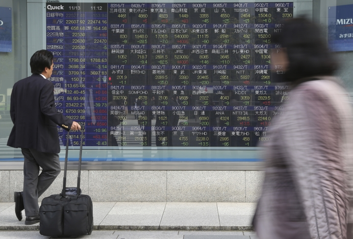 In this Nov. 13, 2017, photo, a man looks at an electronic stock board of a securities firm in Tokyo. Tokyo stocks were marginally higher Tuesday, May 1, 2018, while most other major Asian markets were closed for public holidays. The White House's announcement that it would postpone a decision on imposing hefty tariffs on U.S. imports of steel and aluminum products from some countries helped boost investor sentiment.(AP Photo/Koji Sasahara)