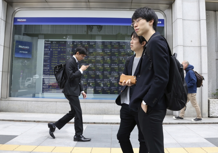 In this April 16, 2018, file photo, people walk by an electronic stock board of a securities firm in Tokyo. Tokyo stocks were marginally higher Tuesday, May 1, 2018, while most other major Asian markets were closed for public holidays. The White House's announcement that it would postpone a decision on imposing hefty tariffs on U.S. imports of steel and aluminum products from some countries helped boost investor sentiment.(AP Photo/Koji Sasahara)