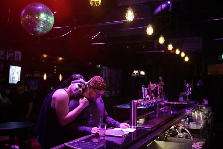 In this Monday, April 30, 2018 photo, Sister Phylliss, left, hugs a patron while hosting Karaoke night at The SF Eagle, a historic gay bar, in San Francisco. San Francisco's gay and leather community is set to get its own cultural district as part of a broader city effort to preserve neighborhoods at risk of disappearing under rising rents. The San Francisco Board of Supervisors will vote on a resolution Tuesday that would create the Leather and LGBTQ District in part of the city's South of Market neighborhood. (AP Photo/Marcio Jose Sanchez)