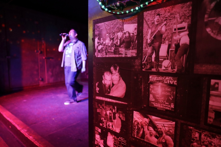 In this Monday, April 30, 2018, photo, photographs decorate a wall next to a stage during karaoke night at The SF Eagle, a historic gay bar, in San Francisco. San Francisco's gay and leather community is set to get its own cultural district as part of a broader city effort to preserve neighborhoods at risk of disappearing under rising rents. The San Francisco Board of Supervisors will vote on a resolution Tuesday that would create the Leather and LGBTQ District in part of the city's South of Market neighborhood. (AP Photo/Marcio Jose Sanchez)