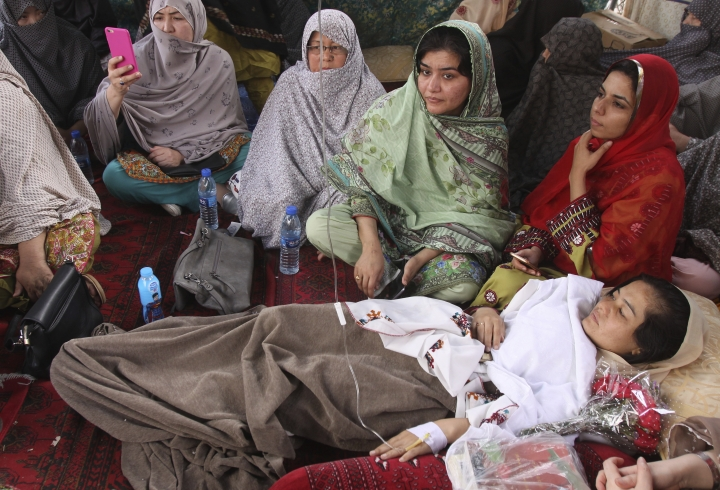 In this Tuesday, May 1, 2018 photo, Pakistani lawyer Jalila Haider, who is on a hunger strike, rests at a camp in Quetta, Pakistan. Haider in Pakistan ended her three-day hunger strike after the country's top general vowed to redouble efforts to protect the Shiite minority, which has been targeted in a string of attacks by Sunni extremists. (AP Photo/Arshad Butt)