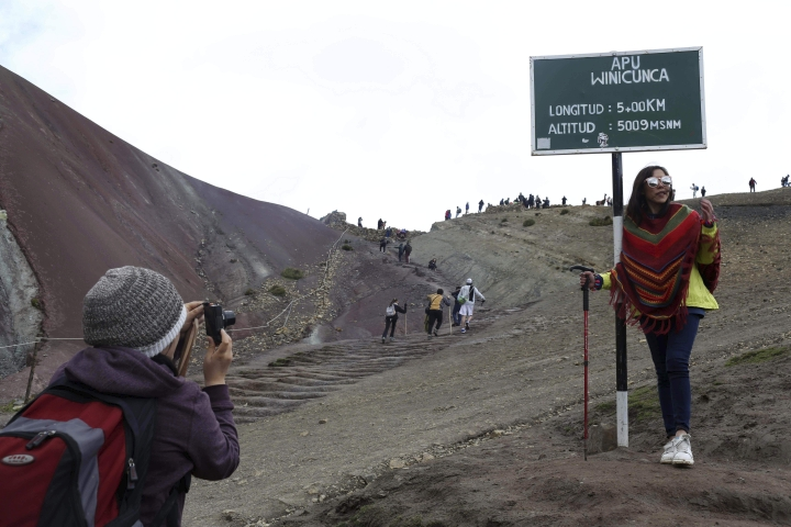 In this March 2, 2018 photo, a tourist poses for a photo at the entrance that leads to Rainbow Mountain, in Pitumarca, Peru. Backpackers are flocking to the dazzling rainbow-colored mountain in the Peruvian Andes, transforming a forgotten village of impoverished alpaca herders into a tourist mecca. (AP Photo/Martin Mejia)