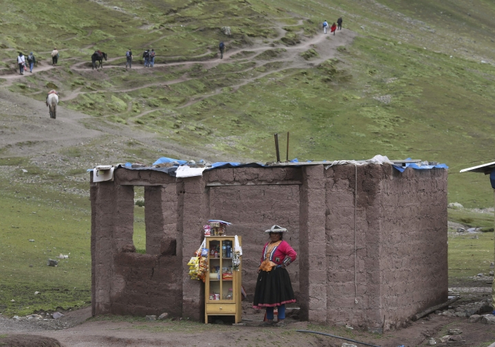 In this March 2, 2018 photo, an Andean woman sell candies, water and chips, on the route to Rainbow Mountain, in Pitumarca, Peru. The popularity of Rainbow Mountain, which attracts up to 1,000 tourists each day, has provided a much-needed economic jolt to this remote region populated by struggling alpaca farmers. (AP Photo/Martin Mejia)