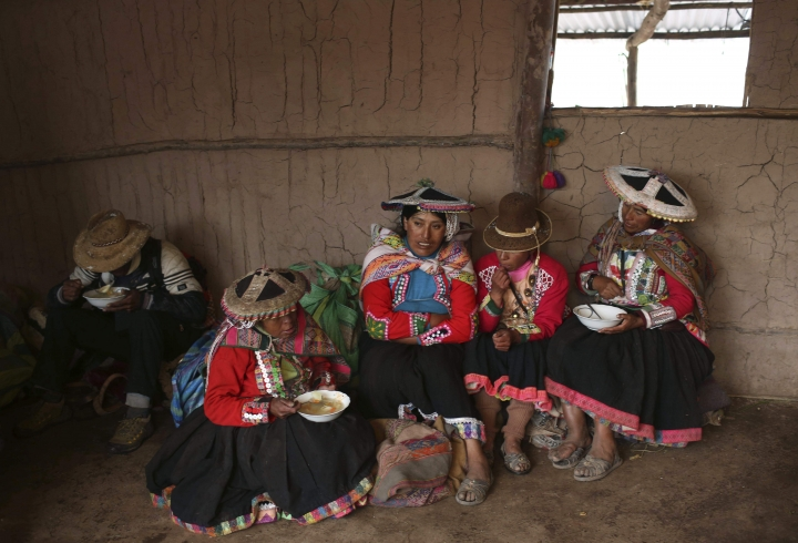 In this April 5, 2018 photo, a group of Andean muleteers break for lunch during a tour guide to Rainbow Mountain, in Pitumarca, Peru. Roughly 500 villagers have returned in the last couple of years to take up their ancestral trade of transporting goods across the Andes. The difference is that now they are hauling tourists on horseback. (AP Photo/Martin Mejia)