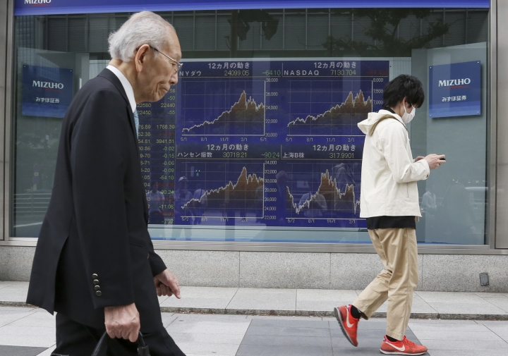 People walk by an electronic stock board of a securities firm in Tokyo, Wednesday, May 2, 2018. Shares are mixed in Asia after a topsy-turvy May Day session on Wall Street, where most benchmarks recovered from early losses as Apple led a rally in technology companies. (AP Photo/Koji Sasahara)
