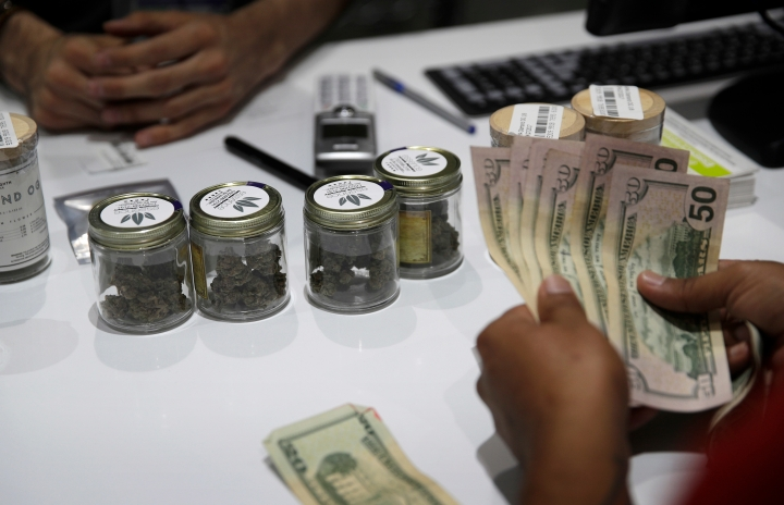 FILE - In this July 1, 2017 file photo, a person buys marijuana at the Essence cannabis dispensary in Las Vegas. Many employers across the country are quietly taking what once would have been a radical step: They're dropping marijuana from the drug tests they require of prospective employees. (AP Photo/John Locher, File)