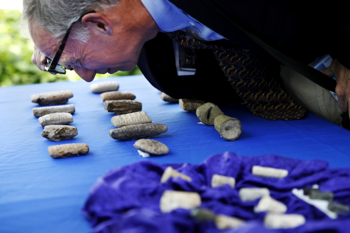 John Russell, an expert on Iraqi antiquities, looks at cuneiform tablets that are being returned to Iraq by Immigration and Customs Enforcement (ICE), during a ceremony at the Residence of the Iraqi Ambassador to the United States, in Washington, Wednesday, May 2, 2018. The artifacts were smuggled into the United States in violation of federal law and shipped to Hobby Lobby stores, a nationwide arts-and-crafts retailer. The shipping labels on these packages falsely described the cuneiform tablets as tile samples. (AP Photo/Jacquelyn Martin)