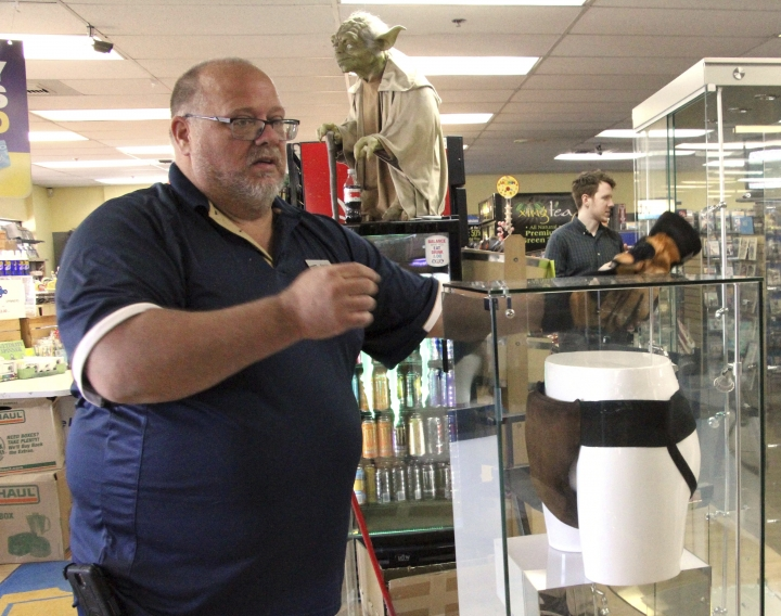 "Blockbuster Alaska General Manager Kevin Daymude moves a display case featuring the jockstrap worn by actor Russell Crowe in the 2005 movie ""Cinderella Man"" at the video store location in Anchorage, Alaska, on Wednesday, May 2, 2018. HBO's John Oliver bought the jockstrap and other items at auction and sent them to Anchorage, in hopes it would help the store stave off pressure from streaming movie services. (AP Photo/Mark Thiessen)"