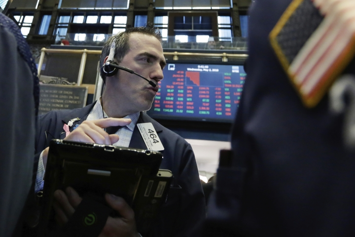 Trader Gregory Rowe works on the floor of the New York Stock Exchange, Wednesday, May 2, 2018. Stocks are opening moderately lower as Wall Street reacts to another big round of company earnings. (AP Photo/Richard Drew)