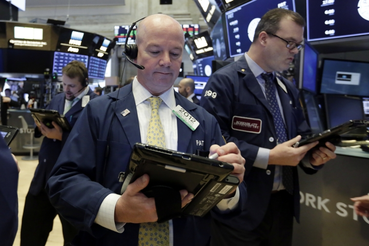 Trader Patrick Casey, center, works on the floor of the New York Stock Exchange, Wednesday, May 2, 2018. Stocks are opening moderately lower as Wall Street reacts to another big round of company earnings. (AP Photo/Richard Drew)