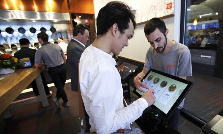 """Charles Renwick lead software engineer at Spyce Food Company, right, assists a customer with an order at the Spyce restaurant, which uses a robotic cooking process in Boston, Thursday, May 3, 2018. Robots can't yet bake a souffle or fold a burrito, but the new restaurant in Boston is employing what it calls a """"never-before-seen robotic kitchen"""" to cook up ingredients and spout them into a bowl. (AP Photo/Charles Krupa)"""