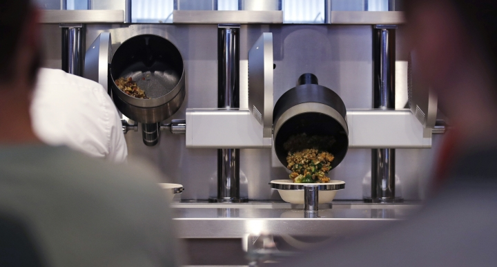 """Customers wait as their automatically prepared food is dropped from a cooking pot into a bowl at Spyce, a restaurant which uses a robotic cooking process in Boston, Thursday, May 3, 2018. Robots can't yet bake a souffle or fold a burrito, but the new restaurant in Boston is employing what it calls a """"never-before-seen robotic kitchen"""" to cook up ingredients and spout them into a bowl. (AP Photo/Charles Krupa)"""