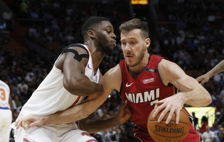 FILE - In this March 21, 2018, file photo, Miami Heat guard Goran Dragic, right, drives against New York Knicks guard Emmanuel Mudiay during the second half of an NBA basketball game in Miami. Dragic is going back to his native Slovenia in a few weeks for summer. There's a couple of weddings that the Heat guard needs to attend, a trip scheduled with his wife to Paris for a fashion show and probably even some pickup basketball to remind his friends that he's an NBA All-Star and they aren't. And there will be some celebrating. Winning the European title last summer is still a huge deal to Slovenians, which means Dragic's homecoming will be a huge deal as well. (AP Photo/Joe Skipper, File)