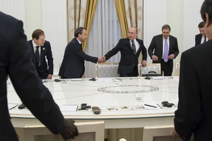 FILE - In this file photo taken on Thursday, April 5, 2018, Russian President Vladimir Putin, second right, shakes hands with Deputy Prime Minister Arkady Dvorkovich, second left, during a meeting at the Kremlin in Moscow, Russia. If Vladimir Putin fulfills the goals he's set for his new six-year term as president, Russia in 2024 will be far advanced in new technologies, many of its notoriously poor roads will be improved, and its people will be living significantly longer. But there's wide doubt about how much of that he'll achieve, if any of it. (AP Photo/Alexander Zemlianichenko, Pool, File)