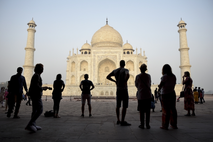 FILE - In this March 22, 2018 file photo, tourists visit India's famed monument of love, the Taj Mahal, in Agra, India. The Taj Mahal, that shining white monument to love, is turning a little green and yellow because of air pollution and swarms of insects, and India's Supreme Court is not pleased. The court has ordered officials to create a plan to ensure the Taj Mahal is properly cared for, and report back by Wednesday, May 9. While officials are cleaning the Taj's exterior with a special clay, the lawyer who brought the case to the court says not enough is being done. (AP Photo/R.S. Iyer, File)