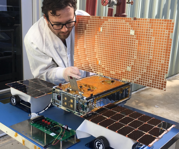 In this undated photo made available by NASA on March 29, 2018, engineer Joel Steinkraus uses sunlight to test the solar arrays on one of the Mars Cube One (MarCO) spacecraft at NASA's Jet Propulsion Laboratory in Pasadena, Calif. The MarCOs will be the first CubeSats - a kind of modular, mini-satellite - flown into deep space. They're designed to fly along behind NASA's InSight lander on its cruise to Mars. (NASA/JPL-Caltech via AP)