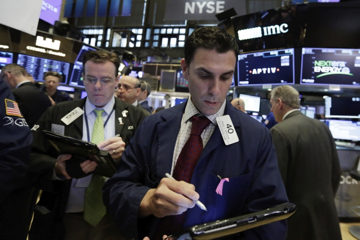 Trader Craig Spector, center, works on the floor of the New York Stock Exchange, Friday, May 4, 2018. U.S. stocks are little changed Friday morning following a slightly disappointing jobs report for the month of April. (AP Photo/Richard Drew)