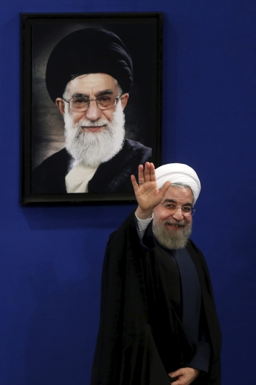 FILE - In this Aug. 29, 2015 file photo, Iran's President Hassan Rouhani waves to reporters at the conclusion of a press conference in Tehran, Iran. President Donald Trump is weighing whether to pull the U.S. out of Iran's nuclear deal, a 2015 agreement that capped over a decade of hostility between Tehran and the West over its atomic program. A picture of Supreme Leader Ayatollah Ali Khamenei hangs on the wall behind Rouhani. (AP Photo/Ebrahim Noroozi, File)