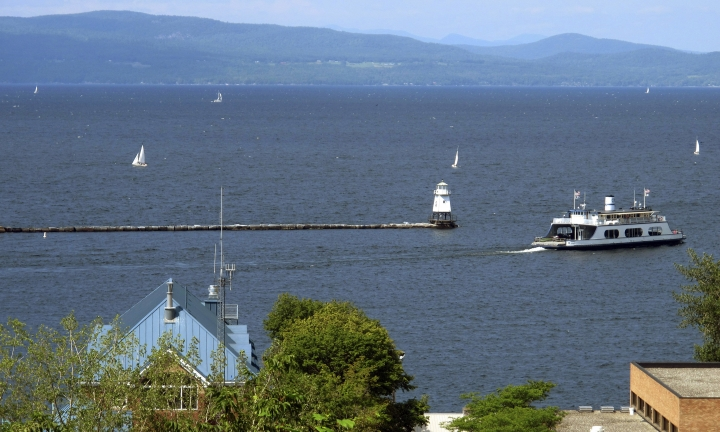 FILE - In this Aug. 14, 2015 file photo, sail boats and a passenger ferry dot Lake Champlain as seen from Battery Park in Burlington, Vt. Two decades after the diminutive lake was ridiculed when it was briefly listed as one of the Great Lakes in 1998, a scientific program that studies the lake between Vermont and New York has been put into the same league as 32 other programs across the country that study those larger lakes. (AP Photo/Wilson Ring, File)