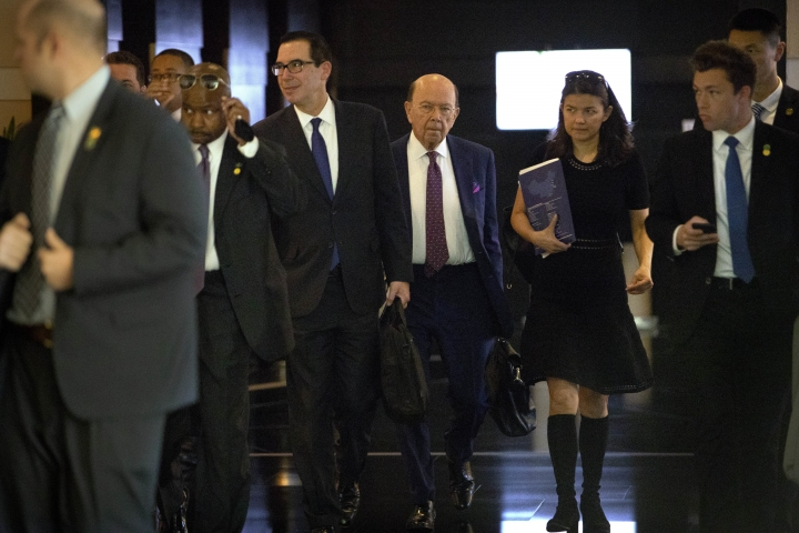 In this May 4, 2018 photo, U.S. Treasury Secretary Steven Mnuchin, center left, and Commerce Secretary Wilbur Ross, center right, leave their hotel in Beijing for trade negotiations with Chinese officials. In a looming trade war between the world's two largest economies, American companies in China may have a bull's-eye on their backs. (AP Photo/Mark Schiefelbein)