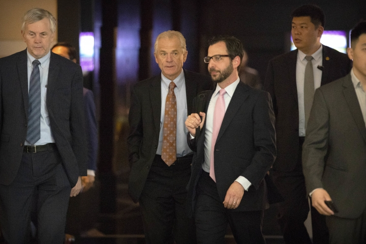 In this May 4, 2018 photo, White House trade adviser Peter Navarro, second from left, leaves his hotel in Beijing for trade negotiations with Chinese officials. In a looming trade war between the world's two largest economies, American companies in China may have a bull's-eye on their backs. (AP Photo/Mark Schiefelbein)