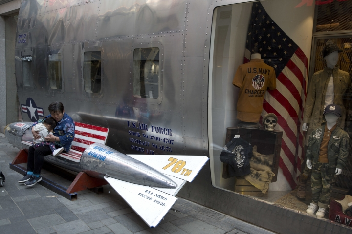 In this April 12, 2018, photo, a woman tends to a child near a promotional gimmick in the form of a bomb and the U.S. flag outside a U.S. apparel shop in Beijing. China's lopsided trade balance with the United States means it will run out of imports for retaliation in a trade spat with Washington before President Donald Trump does. But Beijing has other ways to inflict pain. Chief among those is harassing American companies that make autos, operate restaurant chains, sell computer software and do other business in China's heavily regulated economy. (AP Photo/Ng Han Guan)