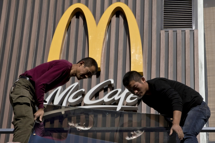 In this Nov. 7, 2017, photo, Chinese workers install glass panels near the logo for US fast food brand McDonald's in Beijing. China's lopsided trade balance with the United States means it will run out of imports for retaliation in a trade spat with Washington before President Donald Trump does. But Beijing has other ways to inflict pain. Chief among those is harassing American companies that make autos, operate restaurant chains, sell computer software and do other business in China's heavily regulated economy. (AP Photo/Ng Han Guan)