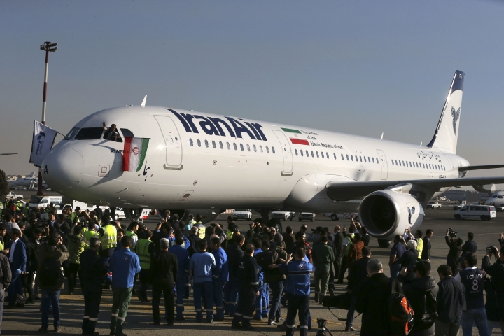 FILE - In this Jan. 12, 2017 file photo, the pilot of Iran Air's new Airbus plane waves a national flag after landing at Mehrabad International Airport in Tehran, Iran. From brand-new airplanes to oilfields, billions of dollars of deals stand on the line for international corporations as President Donald Trump weighs whether to pull America out of Iran's nuclear deal with world powers. (AP Photo/Vahid Salemi, File)